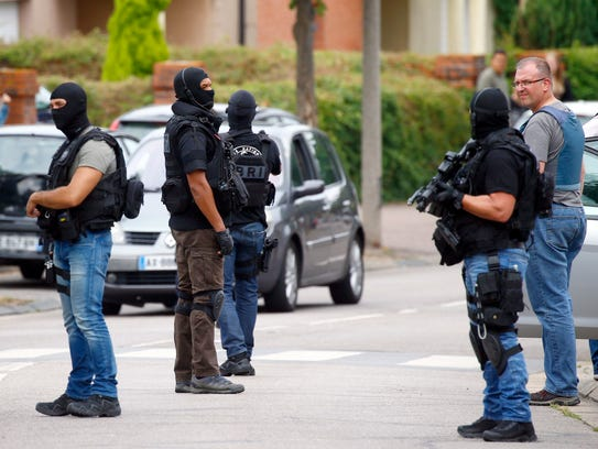 Police officers conduct a search in Saint-Etienne-du-Rouvray,
