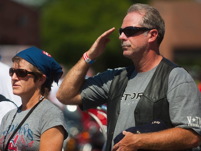 A crowd member stands and salutes as Timothy Arney sings the national anthem during the Memorial Day Ride in Glendale on May 25, 2014.