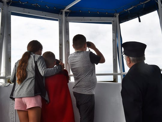 Portraying lightkeeper Henry Gattie, lighthouse authority Ed Miller helps Caitlin, Caigin and Caisin Carlisle of McHenry, Ill., locate the Cana Island Lighthouse off in a distance while on a guided Shoreline Scenic Cruises & Charters lighthouse cruise on July 27.