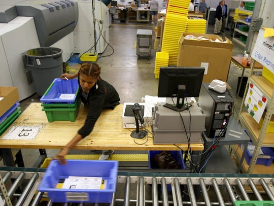 Amelia Robinson of Memphis checks the quality of print jobs at her station on July 7, 2010.
