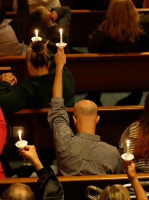 Community members raise their candles in the air Friday, May 19, 2017, during a vigil for 16-year-old Sabrina Ray at First Christian Church in Perry.