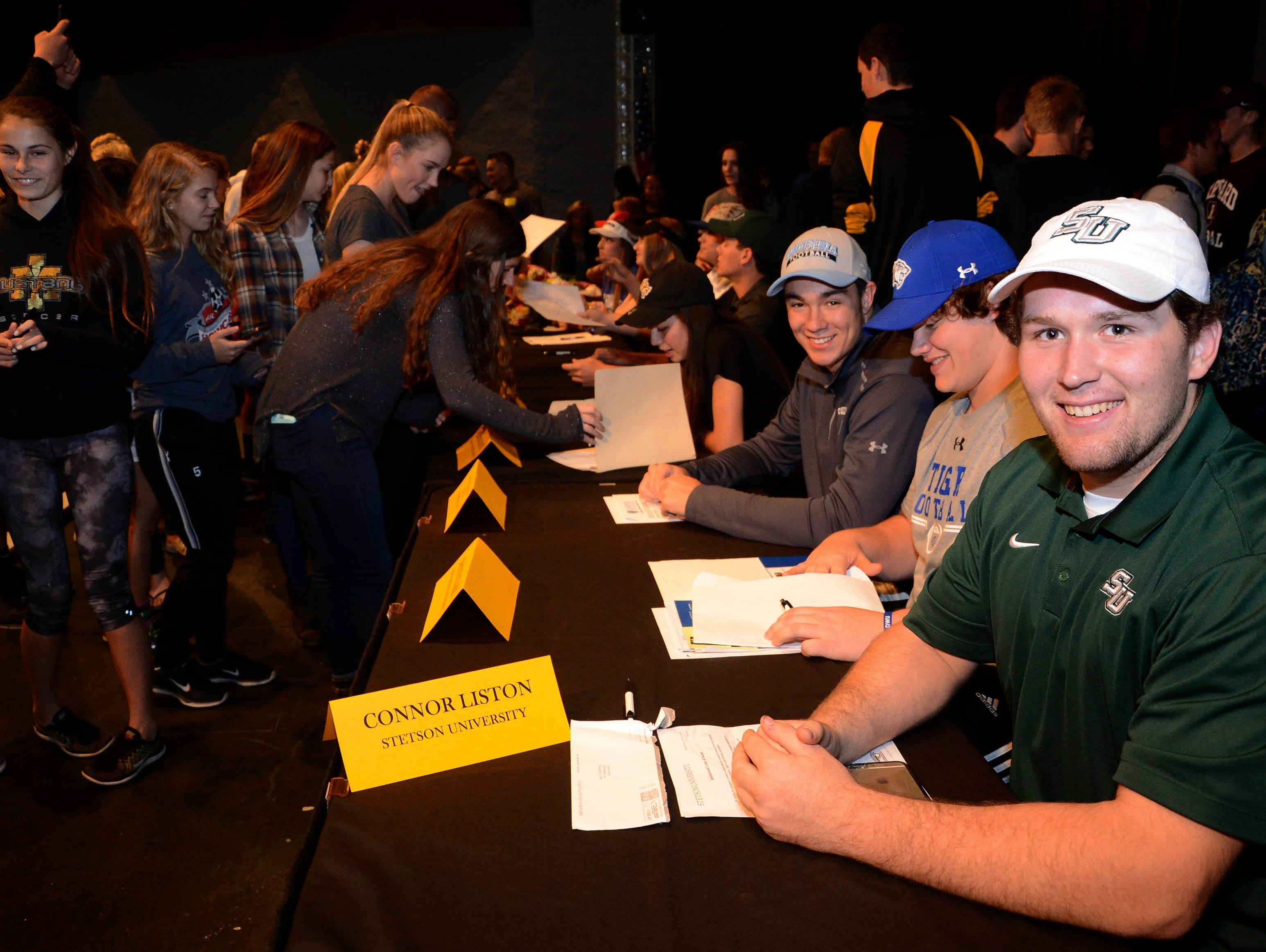 Connor Liston, Dayne Clark and otter seniors at Merritt Island High get their pictures takes after signing their letters of intent in the school auditorium.