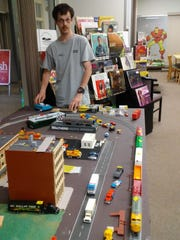 Employee Kevin Gossen poses with model trains inside