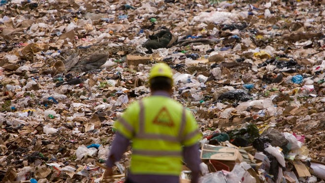 An employee with the Washington County Solid Waste District works at the county landfill in this file photo. Area governments are considering a countywide curbside recycling program in an effort to encourage more people to recycle and cut back on the demands at the landfill.