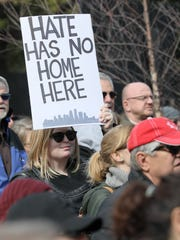 Dani Harper holds a 'hate has no home' sign during
