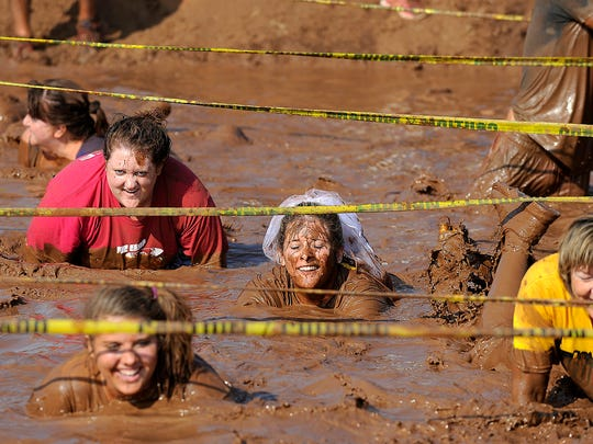 Mindi Gibbs crawls through the final mud pit with members of her wedding party during the third annual Mudslinger Fun Run in 2013.