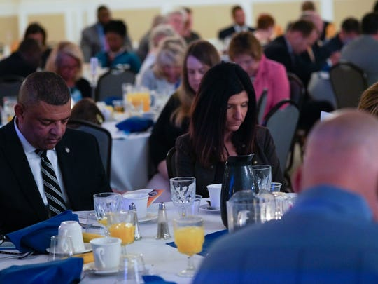 Audience members attending the 58th Annual Delaware Governor's Prayer Breakfast bow their heads in prayer.