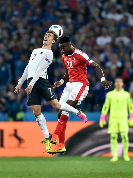 France's Antoine Griezmann, left, jumps for the ball with Switzerland's Johan Djourou during the Euro 2016 Group A soccer match between Switzerland and France at the Pierre Mauroy stadium in Villeneuve d'Ascq, near Lille, France, Sunday, June 19, 2016. (AP Photo/Martin Meissner)