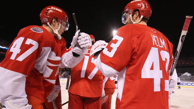 Red Wings defenseman Alexei Marchenko and forward Darren Helm celebrate the game winning goal by Brad Richards, center, during the third period of the Wings' 5-3 win Saturday at Coors Field.
