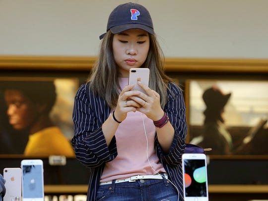 A woman looks at an iPhone 8 Plus at an Apple Store in San Francisco, Sept. 22, 2017.