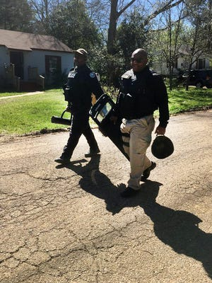 Law enforcement officers leave the scene of a  suspect search in Jackson, Miss.