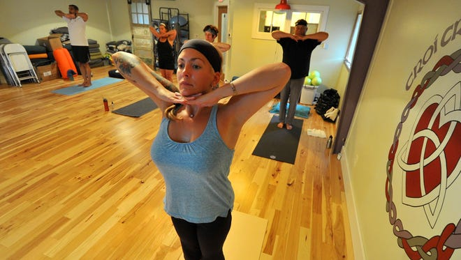 Casey Nick of Wausau practices yoga with a group Thursday, July 30, 2015, at Croi Croga Studio in Wausau.