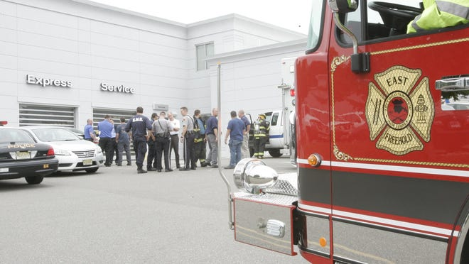 Emergency personnel gather in front of the service center of DcH Freehold Nissan, in Freehold Township, Friday afternoon, following a hazardous material leak inside the building which made people fill ill.