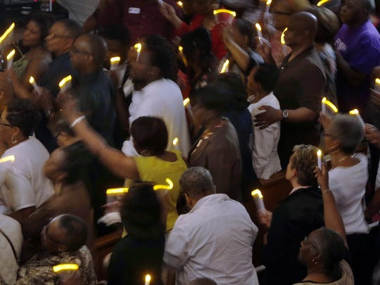 Worshipers sway with music as they hold electric candles in a darkened sanctuary Thursday during a prayer service at Bethel AME Church in Wilmington in the wake of the Charleston, S.C., church shootings.