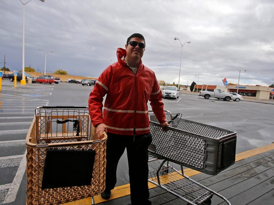 Taylor Kempton retrieves shopping carts on Nov. 3 at the Safeway on West Main Street in Farmington.