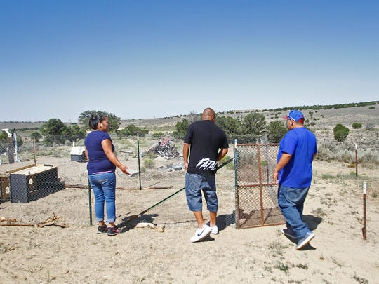 From left, Clarissa Murphy, Jamey Murphy and Jerry Francisco inspect a chicken pen on Friday at their home in Nageezi after the family was allowed to return to the house. They were forced to evacuate on Monday night after a fire broke out at a nearby WPX Energy oil production site.