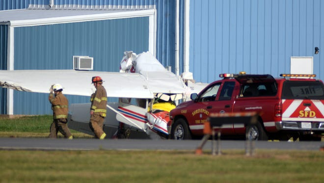 Emergency personnel tend to a single engine Cessna that crashed Friday afternoon while its pilot reportedly was doing touch and go exercises at Shreveport Downtown Airport. The pilot was killed in the crash.