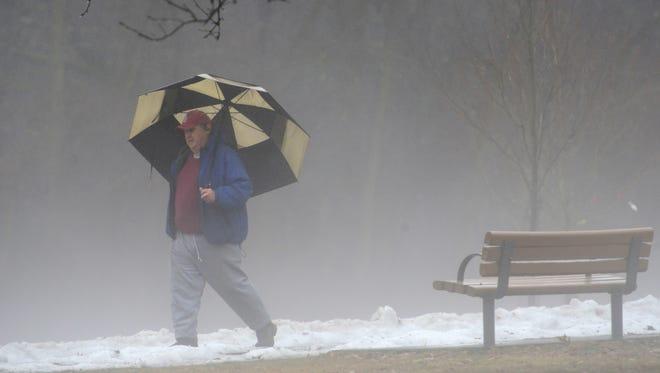 Dave Parish, of Wayne, walks through the fog and rain at the Saddle River County Park in Glen Rock Friday morning January 12, 2018.