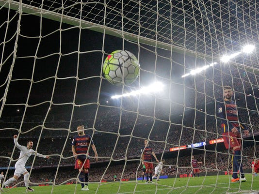 Barcelona goalkeeper Claudio Bravo, right, and Gerard Pique, 2nd right, watch the ball hit the net after Real Madrid's Cristiano Ronaldo scored the winning goal during a Spanish La Liga soccer match between Barcelona and Real Madrid, dubbed 'el clasico', at the Camp Nou stadium in Barcelona, Spain, Saturday, April 2, 2016. Real Madrid won  2-1. (AP Photo/Manu Fernandez)