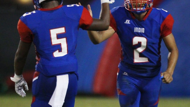 At left, Indio High School's Nathaniel Donte congratulates his team mate Jose Perez after a scored touchdown by Perez agains Desert Mirage High School at Ed White Stadium in Indio on August 25, 2017.