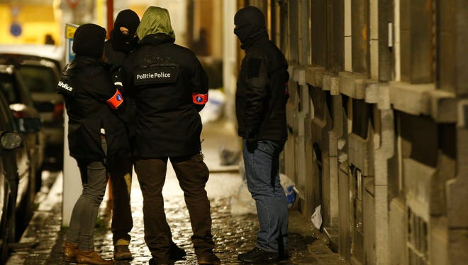 Policemen guard the outside of a house that has been the subject of a police raid in the suburb of Schaerbeek in Brussels on March, 25, 2016. Security forces have continued raids in several cities, rounding up terror suspects.