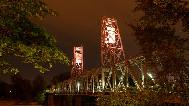 Lights cast an orange glow on the Union Street pedestrian bridge to raise awareness for work zone safety.
