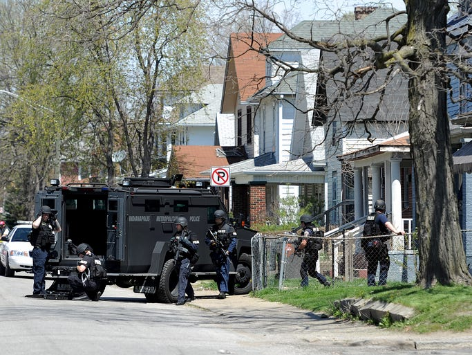 The SWAT team works to get a man out of a barricaded duplex on the 100 block of N. Gray Street, Sunday, April 20, 2014, in Indianapolis.