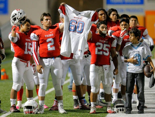 North Salinas' Timothy Burkhardt and Armando Armenta hold the jersey of Carlos Robles before a game against Salinas at Rabobank Stadium in this file photo. Robles, a sophomore defensive end on the North Salinas football team, was shot and killed in 2015.