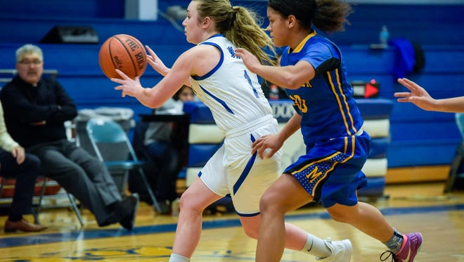 Kaitlyn Borghesi (1) of Donovan passes as Lyric Green (10) of Manchester defends. Manchester's Lyric Green (10) Manchester Girls played basketball at Donovan Catholic in Toms River on Tuesday, January 12,2016. /Russ DeSantis for the Asbury Park Press / Slug: ASB 0113 girls hoops wrap