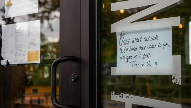 """A sign is taped to the door telling customers to """"Please wait outside"""" for their orders at Hudson Taco, on Monday, in the City of Newburgh."""