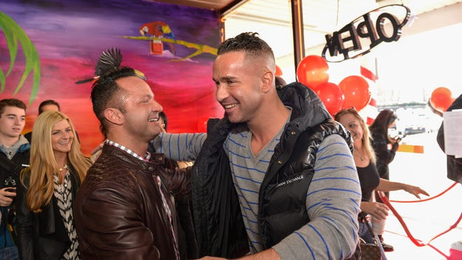 """Mike """"The Situation"""" Sorrentino (center) greets his brother Frank (left) at the opening   of their Middletown tanning salon, Boca Tanning Club, on March 1."""