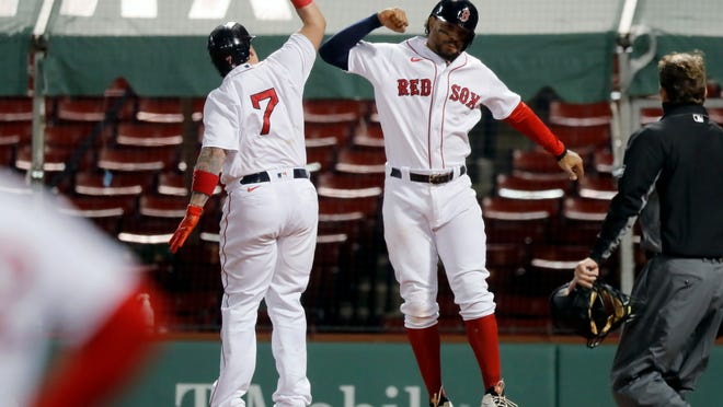 Boston Red Sox's Christian Vazquez, left, celebrates his three-run home run that also drove in Xander Bogaerts, right, during the sixth inning of a baseball game against the Baltimore Orioles, Tuesday, Sept. 22, 2020, in Boston.