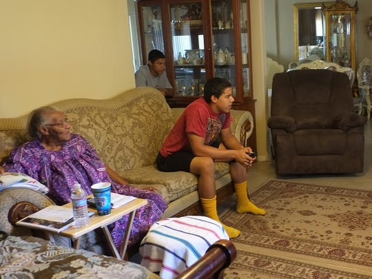 Tyler and Tayler Hawkins watch a football game being re-played on the television with their grandmother, Wessie Mae Roy.