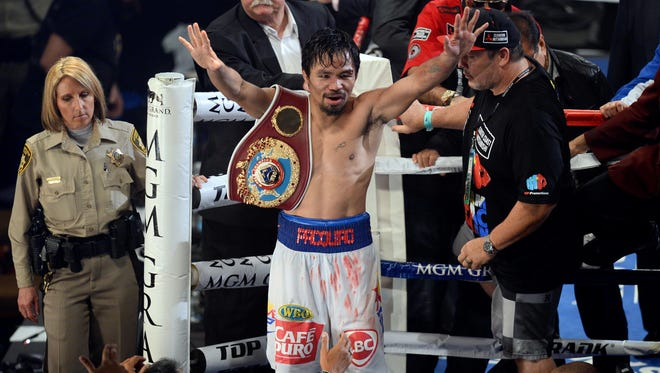 Manny Pacquiao celebrates after defeating Tomothy Bradley Jr. (not pictured) in their WBO World Welterweight Title bout at MGM Grand Garden Arena. Pacquiao won via unanimous decision.