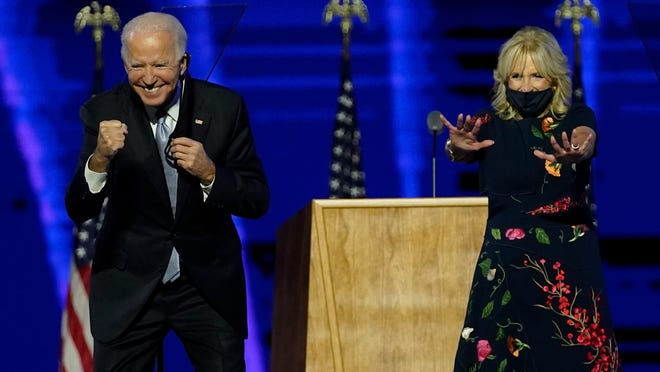 President-elect Joe Biden and wife Jill Biden gesture to supporters Saturday, Nov. 7, 2020, in Wilmington, Del.