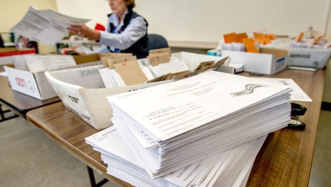 Election judge Karen Brenkman sorts through piles of mail-in ballots on Tuesday at the McKenzie Building in Pekin. The ballots are opened, verified and then fed into ballot boxes in groups of 100.