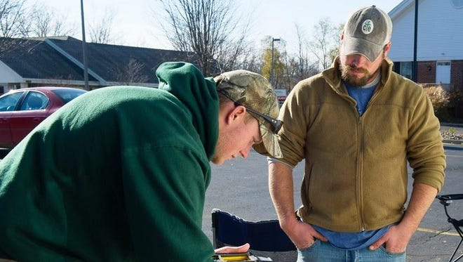 A hunter checks in a deer at a Michigan Department of Natural Resources check station in the Lower Peninsula.