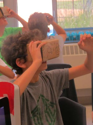 Hartshorn School fourth-grader Reese Cohen reaches into a virtual world during a Google Expedition to a barrier reef in teacher Susan Mustion's classroom May 20.