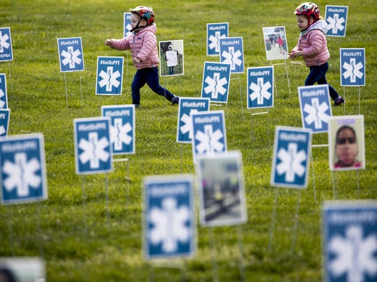 File - Children run though a thousand signs made by the advocacy group MoveOn along with other organizations that read #GetUsPPE, along images of health care workers, a call for personal protective equipment for health care workers during the coronavirus outbreak, on the West Lawn of the U.S. Capitol, Friday, April 17, 2020, in Washington.