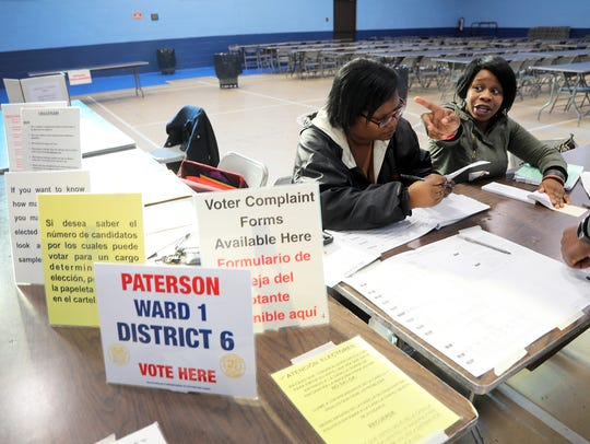 Poll workers Calandra Matthews and Melisa Morgan help voters sign in at the St. Joseph's Community Center in Paterson last November.