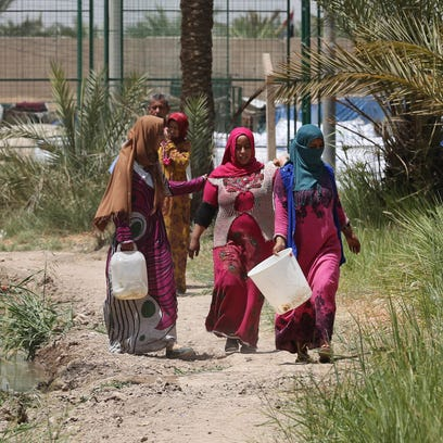 Iraqis displaced by conflict walk on a path on their way to collect water at al-Takia refugee camp in Baghdad, Iraq, Thursday, July 30, 2015. Scorching temperatures are normal this time of year, but an unprecedented heat wave prompted Iraqi authorities to declare a mandatory four-day holiday beginning Thursday.