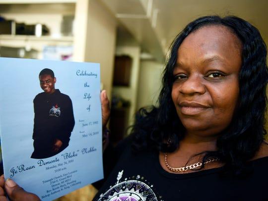 Lyvonne Cargill, 47, holds the obituary program from