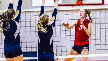 Willow Martin (right) of Mason hits through a block by MacKenzie Housler (5) and Madison Jaqua (center) of Portage Central during their Class A regional semifinal match.