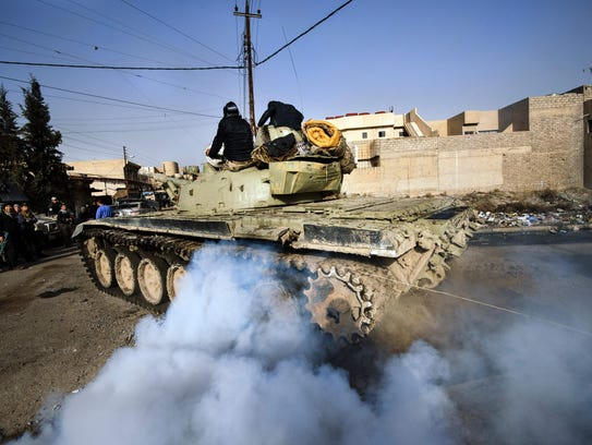 An Iraqi army T-72 tank heads to the front line during