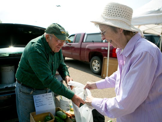 """Ray Hoffman of Auburndale, left, puts cucumbers in a bag for Maryanne Konitzer of Marshfield at the Main Street Marshfield Farmers' Market at the Pick 'N Save parking lot in Marshfield,Tuesday, July 29, 2014. Konitzer was buying cucumbers from Hoffman because they are second cousins """"somewhere down the line."""" The Main Street Marshfield Farmers' Market runs every Tuesday from 9 a.m. to 1 p.m. through September 30."""