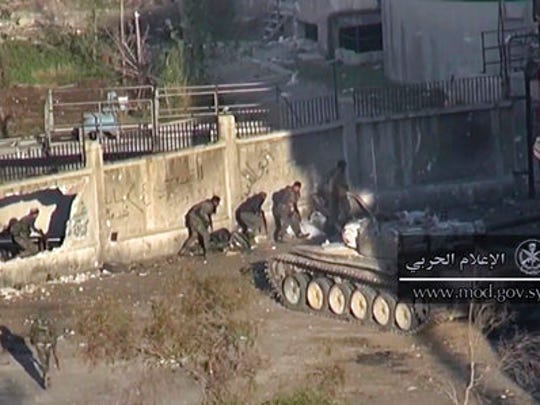 This frame grab from video provided by the government-controlled Syrian Central Military Media, shows Syrian troops taking up positions during fighting with insurgents, in an eastern neighborhood of Damascus, Syria, Wednesday, March. 22, 2017. Syrian troop are engaged in fighting with insurgents who have tried to breach government lines in eastern neighborhoods of the capital this week. The operation is spearheaded by the al-Qaida-linked Levant Liberation Committee.