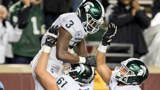 MSU offensive tackle Cole Chewins lifts up running back LJ Scott after his second touchdown Saturday, giving the Spartans a 30-13 lead.
