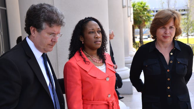 Marissa Alexander is flanked by her lawyers as they speak to the media, in Jacksonville, Fla. Alexander claimed self-defense after prosecutors say she fired a gun at her estranged husband and his two sons. She went to jail.