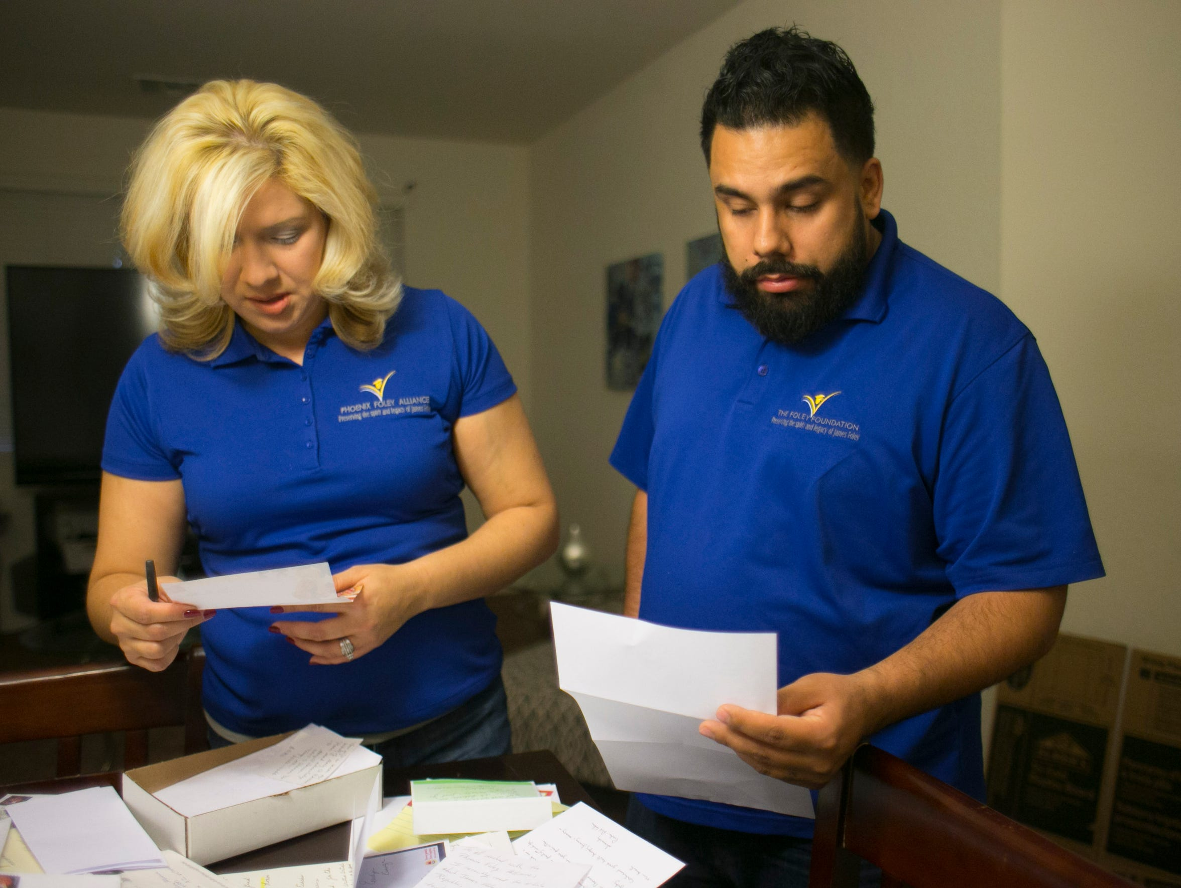 Kristen Martinez and Eddie Martinez look at letters that people sent them with checks to support their foundation, the Phoenix Foley Alliance, in December 2015.
