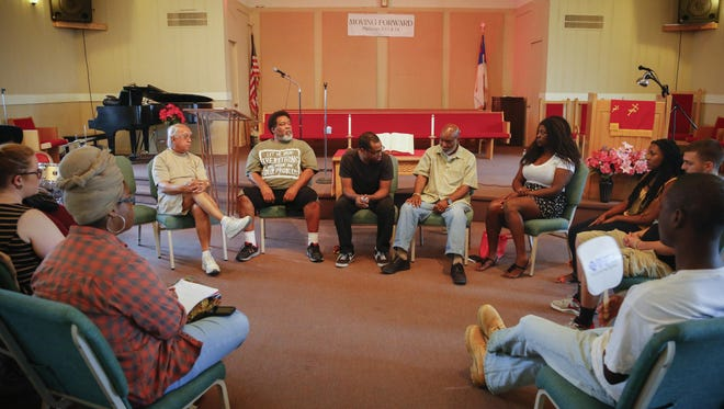 Arnold Woods III, center, leads a vigil at the Faith Missionary Baptist Church Thursday, June 18, 2015, held in response to the shooting in South Carolina on Wednesday evening.